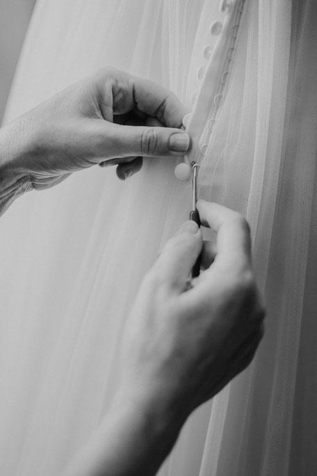 Knöpfe am Brautkleid werden von der Brautmutter mit Häkelnadel geschlossen