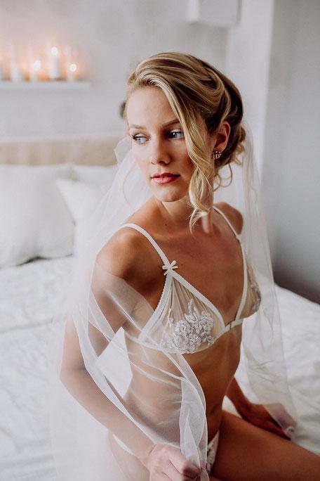 Braut sitzt in Spitzenwäsche auf dem Bett bei Fotoshooting in Nackenheim