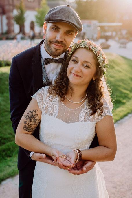 Braut und Bräutigam mit Eheringen im Sonnenuntergang