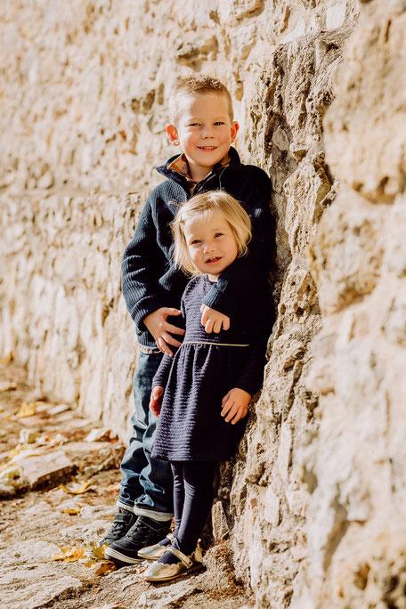Bruder und Schwester lehnen an eine Mauer
