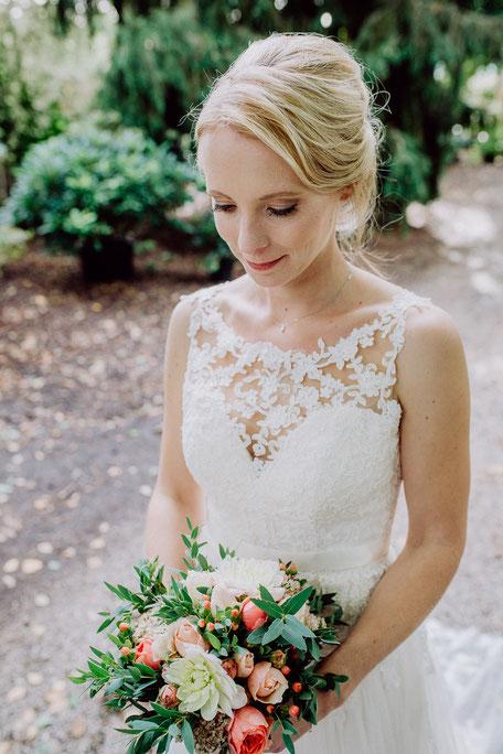 Braut schaut auf ihren Brautstrauss bei First Look Shooting