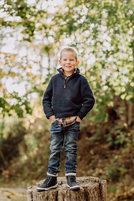 Junge in Jeans und Pullover steht lächelnd auf einem Baumstumpf