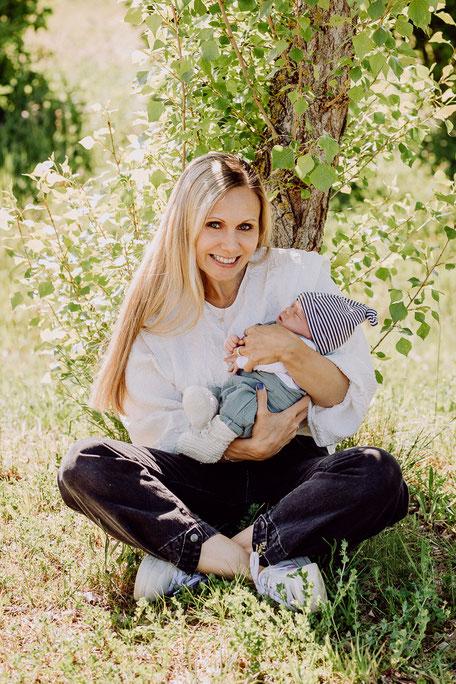 Mutter sitzt mit neugeborenem Sohn unter einem Baum