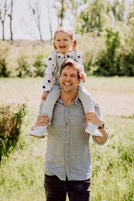Mädchen sitzt auf den Schultern des Vaters und lacht