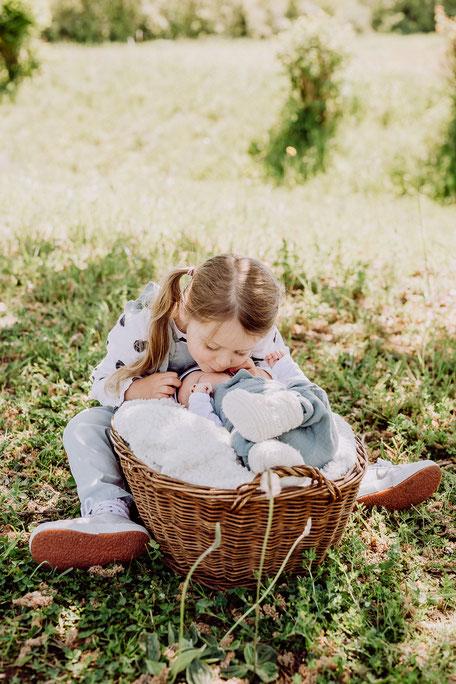 große Schwester küsst Baby auf die Wange bei Fotoshooting