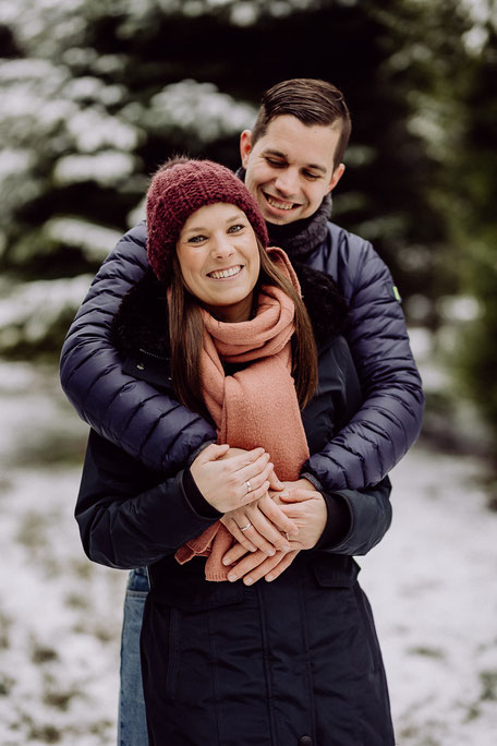 Mann umarmt lächelnde Frau von hinten