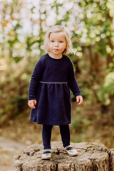 Kleines Mädchen in blauem Kleid steht auf Baumstumpf