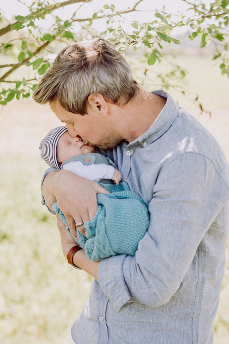 Vater küsst Neugeborenes auf seinem Arm