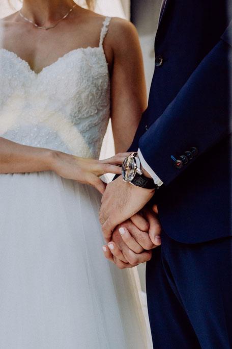 Braut und Bräutigam halten sich an der Hand