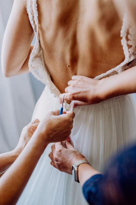 Das Brautkleid wird am Rücken zugeknöpft beim Getting Ready in der Nähe von Mainz