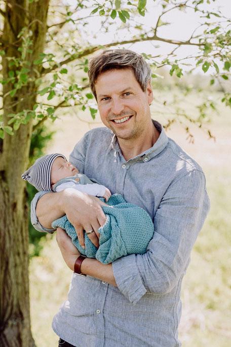 Vater mit Baby auf dem Arm unter einem Baum