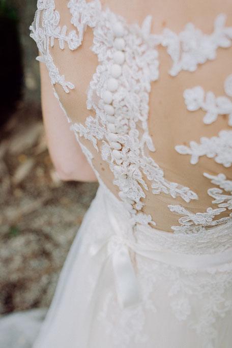 Rückenausschnitt des Brautkleides mit Knopfleiste und Spitze bei Brautpaarshooting