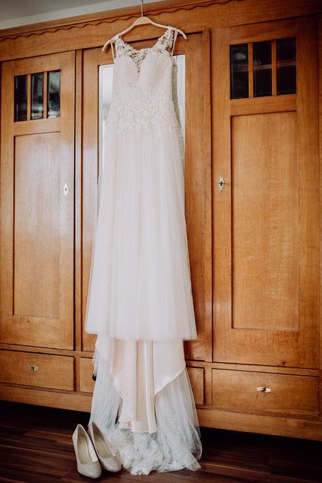 Spitzenbesetzes Brautkleid hängt am Holzkleiderschrank bei Hochzeitsreportage