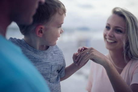 Kind wird von Papa getragen und hält Mamas Hand