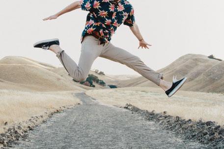 Mann springt über Kiesweg