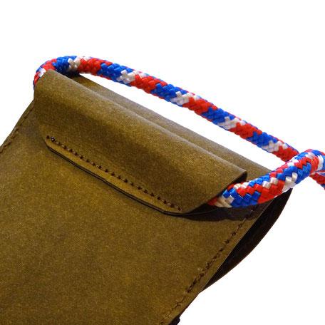 Handtasche von hinten mit rot weiß blauer Kordel.