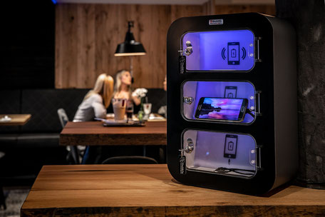 Dock&Go UP Handy Ladestation in schwarz platziert in einem Restaurant / in einer Bar.