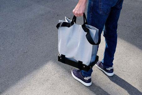 Basket - Universal Design bag project - Man standing while holding a grey basket bag - wheelchair bag - tote bag