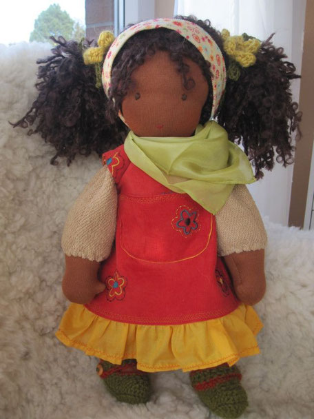 Die Puppe für Aminata trägt ein mit Blüten besticktes Kleid aus rostorangem Feincord u. Rüschenkante aus Bio-Batist, Häkelschühchen (und -mütze) aus weichem Alpakagarn, Halstuch aus pflanzengefärbter Seide
