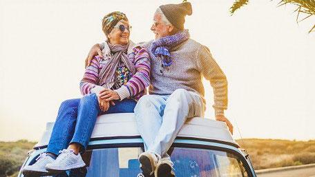 Ein älteres Paar, Oma und Opa, sitzen in bunten Sachen und mit Jeans und Mütze auf einem blauen Auto unter Palmen in der Sonne.