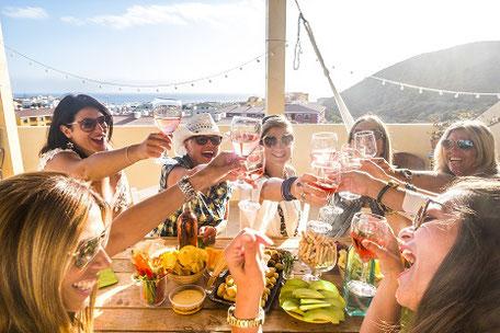 Gruppe von fröhlichen Menschen stösst mit Gläsern an während einer Gruppenreise im Urlaub unter der Sonne