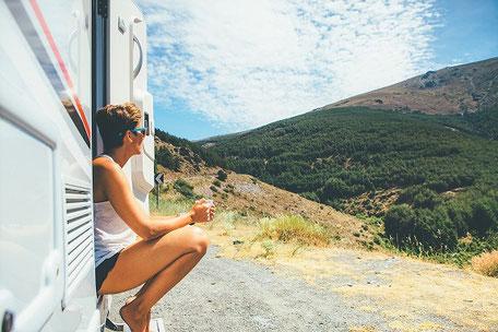 Frau sitzt entspannt in der Tür ihres Wohnmobils mit einer Tasse in der Hand und schaut in die Berge