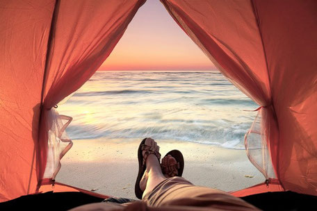 Aufwachen im Zelt direkt am Strand mit der aufgehenden Sonne im Campingurlaub