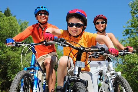 Vater, Mutter, Kind. Die ganze Familie fährt Fahrrad im Urlaub mit dem RundumSorglos-Schutz und Fahrrad-Versicherung der ERGO gegen Diebstahl und Beschädigung auf Reisen.