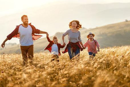 Glückliche Familie mit zwei kleinen Kindern läuft Händchen haltend durch ein Feld im Deutschland-Urlaub.