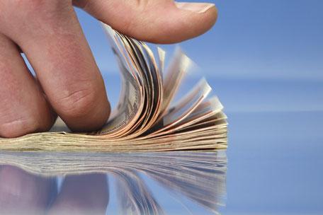 Ein Daumen geht über einen Stapel Euroscheine als Synonym für eine Reiserücktrittskosten-Versicherung