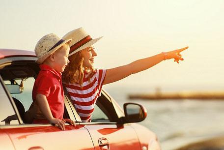 Eine Mutter fährt mit ihrem Sohn mit dem roten Auto in den Urlaub, beide haben Strohhüte auf und ein rotes T-Shirt an.