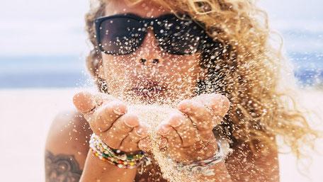 Frau mit blonden Haaren und bunten Armreifen sitzt am Strand und pustet Sand in die Luft