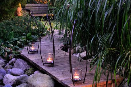 Windlicht Vincent aus Metall mit Glas, sehr schön geschwungene Metallstäbe geben ein ruhiges Licht, welches zu Träumen einlädt und Ihre Terrasse oder Balkon in ein angenehmes warmes Licht taucht.