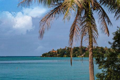 Blick in einer Bucht übers Meer zu Bungalows zwischen Palmen