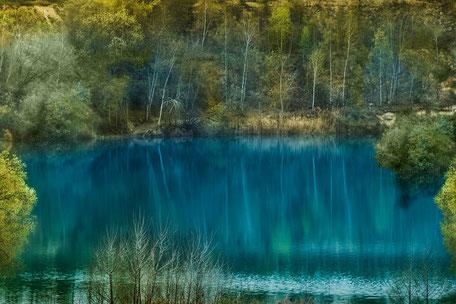 Bäume speigeln sich in türkisfarbenen See
