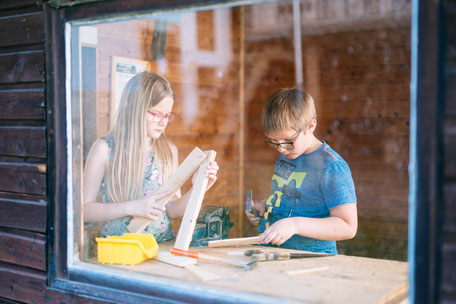 Junge sägt ein Brett in der Kinderwerkstatt am Biobauernhof Stadler