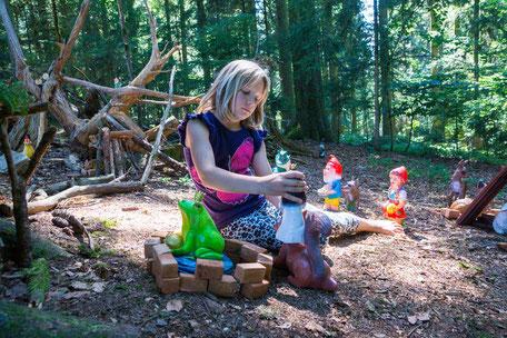 Mädchen spielt im Sonnenschein mit Märchenfiguren im Zwergenwald am Biobauernhof Stadler