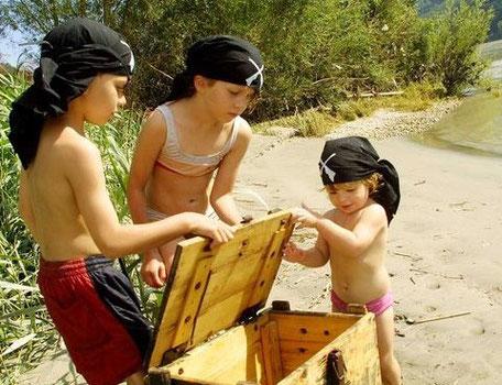 Als Piraten verkleidete Kinder beim öffnen der Schatzkiste