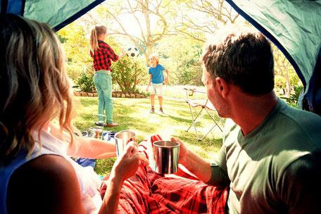 Familie mit zwei Kindern auf dem Campingplatz im Zelt, gut geschützt mit Camping-Reiseversicherung-Campingplatz-Schutz