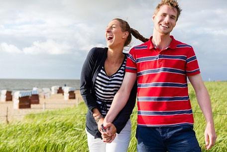 Ein Mann und eine Frau laufen entspannt im Deutschlandurlaub durch Dünen an der Küste und lachen beide. Im Hintergrund Strandkörbe. Sie haben sich gut versichert bei der ERGO Reiseversicherung.