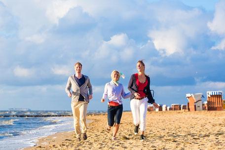 Ein Mann auf dem Weg zum Meer bei strahlend blauem Himmel im Deutschlandurlaub mit Reiseschutz-Reiseversicherung der ERGO