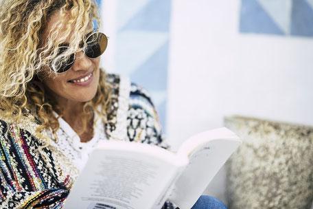 Ein Frau mit blonden Locken und Sonnenbrille liest in einem Buch und lernt für eine Seminarprüfung gut mit Seminar-Versicherung