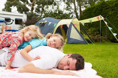 Zwei Kinder liegen entspannt auf ihrem Vater auf der Wiese im Campingurlaub auf einem Campingplatz und lachen. Im Hintergrund ein Zelt und ein Womo. Sie haben sich gut versichert bei der ERGO Reiseversicherung.