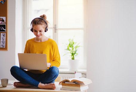 Eine junge Frau sitzt mit Laptop und Kopfhörern auf dem Sofa und lernt für ein Seminar, gut versichert bei der ERGO Reiseversicherung mit einer Seminarversicherung.