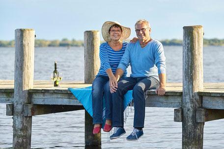Ein Mann und zwei Frau laufen am Strand am Meer bei strahlend blauem Himmel im Deutschlandurlaub