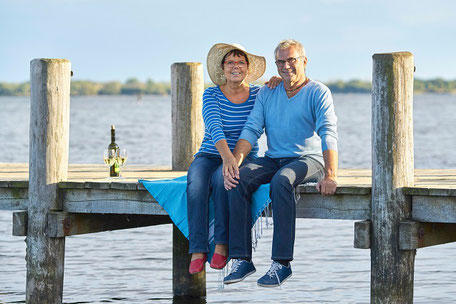 Ein Mann und zwei Frau sitzen am See bei strahlend blauem Himmel im Deutschlandurlaub