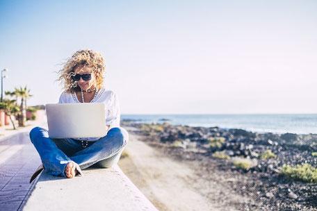 Weltenbummlerin und Influencerin auf der Kaimauer am Meer mit Laptop beim arbeiten im Ausland mit Langzeit-Krankenversicherung