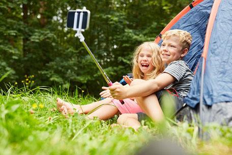 zwei Kinder sitzen vor einem Zelt, machen Selfies und lachen. Hoffentlich haben die Eltern eine Camping-Versicherung