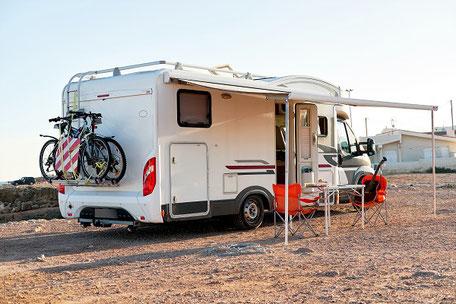 Wohnmobil mit Campingtisch und Stühlen davor und Fahrräder dabei, gut versichert mit ERGO Wohnmobil-Reiseschutz und Sportgeräte-Versicherung