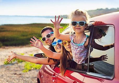 Endlich Urlaub: Eine Familie mit zwei Kindern fährt mit einem roten Auto ans Meer in den Urlaub an die Küste. Sie lachen und freuen sich und sind gut versichert mit dem richtigen Reiseschutz - der Storno-Versicherung gegen Rücktrittskosten.